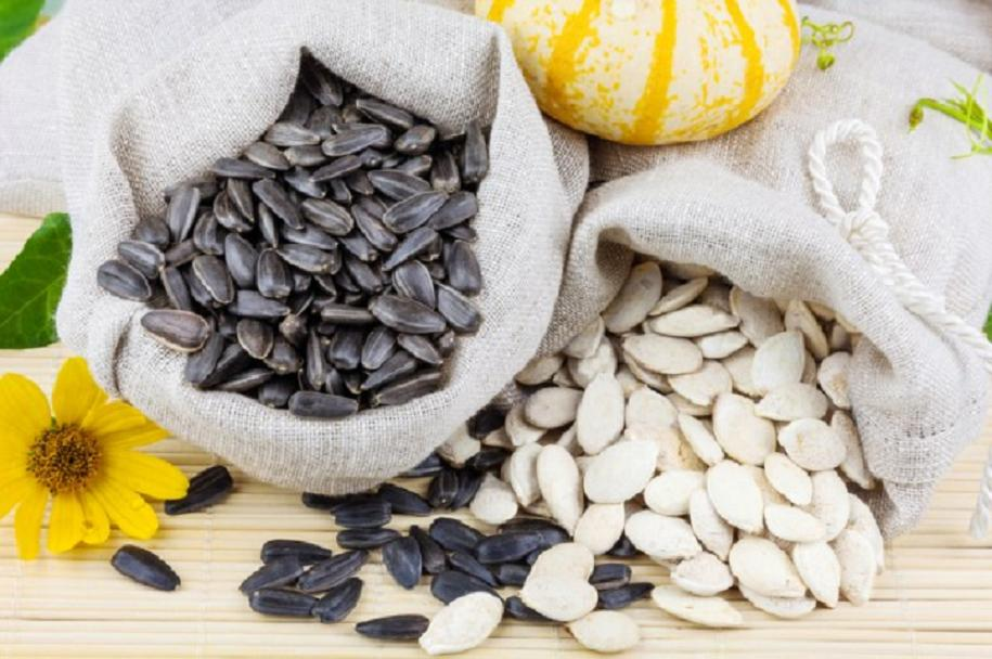 Macro view of raw sunflower and pumpkin seeds in flax sacks with flower and pumpkin on the mat
